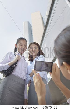 Businesswoman taking photo of her co-workers with her cell phone