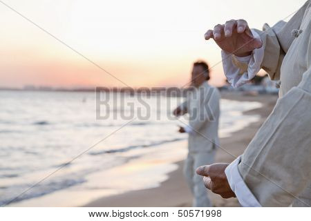 Two older people practicing Taijiquan on the beach at sunset, close up on hands