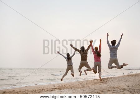 Young Friends Jumping at the Beach