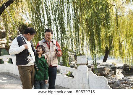 Multi-generational men walking with fishing gear at lake