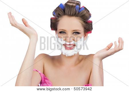 Cheerful woman with hands up and shaving foam on face on white background