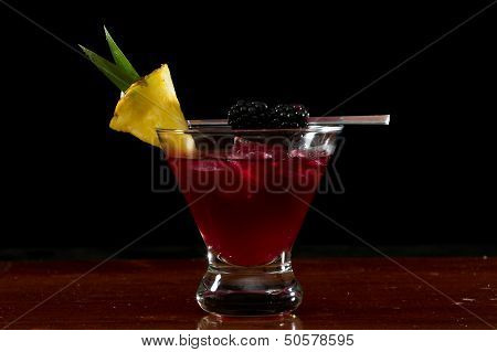 cocktail served in a stemless martini glass garnished with a pineapple slice and blackberries poster