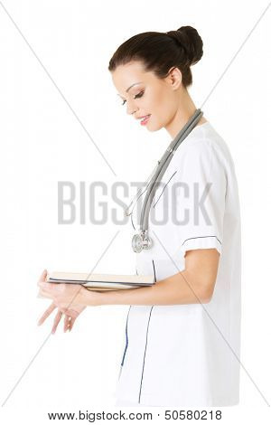 Attractive medicine student or doctor reading book ( treatise ), isoalted on white