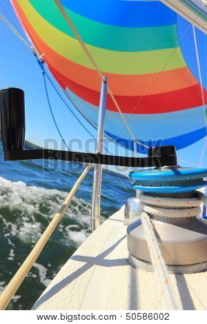 The wind has filled the spinnaker on sailing yacht. Detail of a colorful sail against the deep blue sky. poster