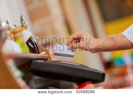 Close-up image of cashier male hands holding card
