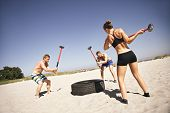 Three strong athletes doing hammer strike on a truck tire during exercise outside on beach. Muscular active people in 20s training to maintain healthy lifestyle poster