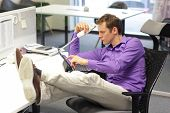 Young businessman caucasian in his office on phone working with tablet - bad sitting posture  poster