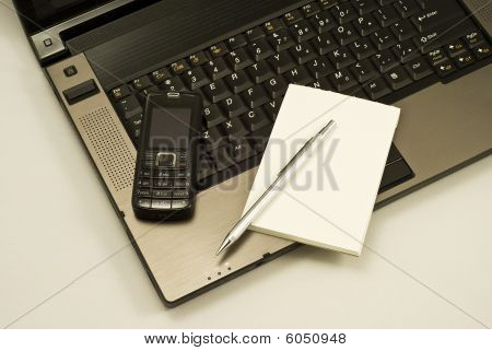Mobile Phone And Notebook On A Laptop