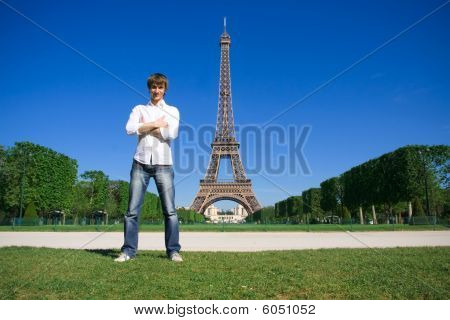Young man standing on the Champs de Mars. Eiffel tower in background poster