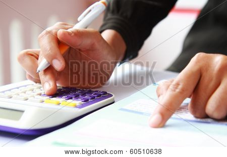 Woman's Hands With A Calculator And A Pen