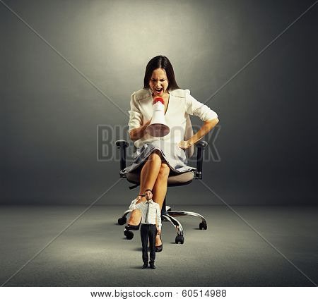 dissatisfied businesswoman screaming at small man with gun over dark background