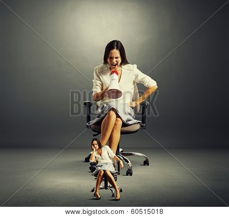 emotional businesswoman screaming at fatigued woman over dark background