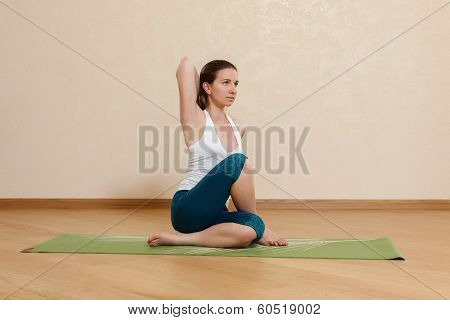 Caucasian Woman Is Practicing Yoga At Studio (gomukhasana)