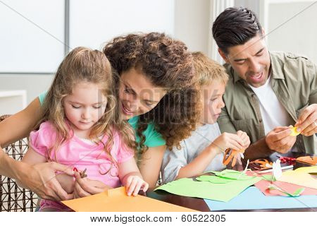Cheerful family doing arts and crafts together at the table at home in kitchen