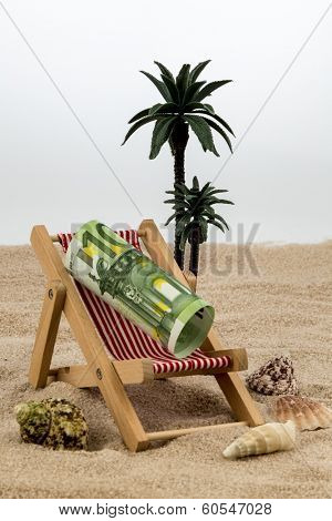 a deck chair with a euro banknote. symbolic photo for saving on holiday and when traveling