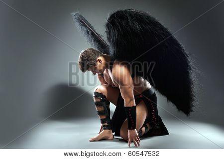 Studio shot of handsome man posing as fallen angel
