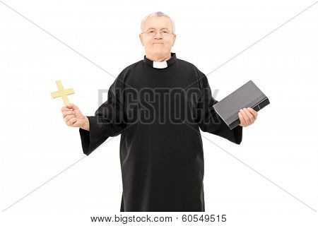 Mature reverend in black mantle holding bible and a cross isolated on white background
