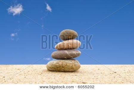 The Balanced Stones On Sand Against The Blue Sky