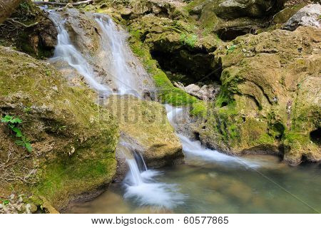 Beautiful waterfall in the forest flowing through the mossy rocks