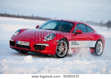 LEVI, FINLAND - FEB 20: Unknown driver powerslides a PORSCHE 911 CARRERA 4S car during Porsche Driving Experience Snow & Ice Press Event on February 20, 2014 in LEVI, FINLAND