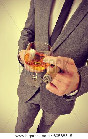 a man wearing a suit with a cigar and a glass with brandy whit a retro effect