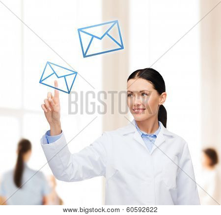 healthcare, medicine and technology concept - smiling female doctor pointing to envelope