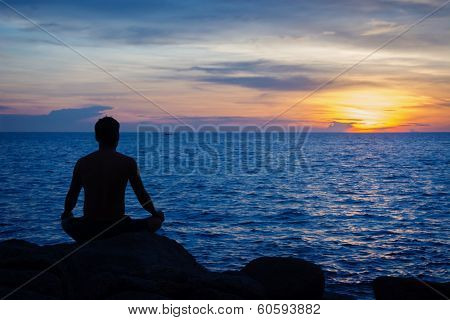 Young Man Practicing Yoga On Ocean Shore