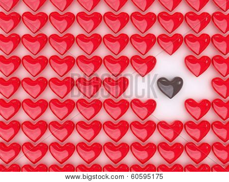 Chocolate heart between a pile of red hearts