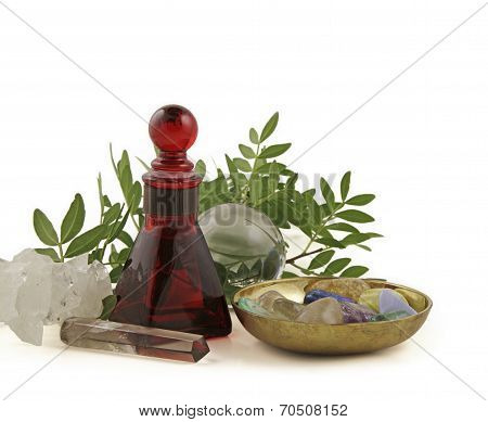 Red glass essential oil bottle, healing crystals in brass dish, crystal ball, smokey quartz wand, apothylite cluster and Bearberry cuttings on a white background poster