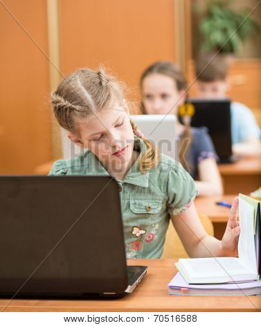 School Kids Using Notebook At Lesson