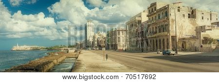Street scene in Old Havana with old decaying buildings at Malecon and the El Morro castle
