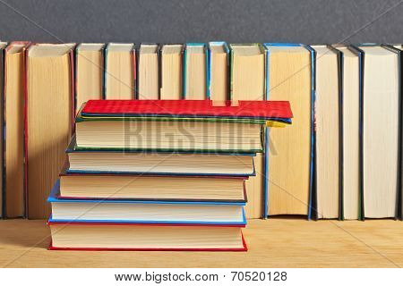 Pile Of Books On A Wooden Surface Against The Background Of A Number Of Books.