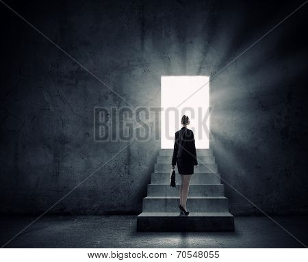 Silhouette of businesswoman with briefcase standing in doorway