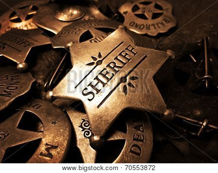 Sheriff's tin badge in pile of star law enforcement badges poster
