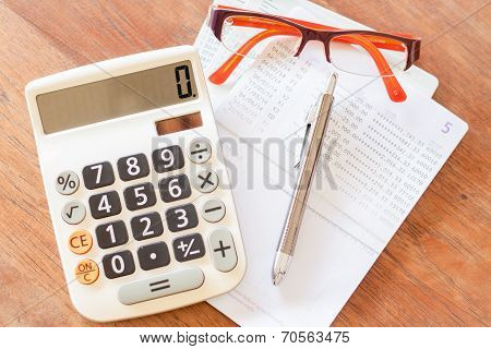 Top View Of Calculator, Pen, Eyeglasses And Bank Account Passbook