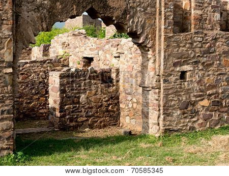 Mugal architecture styled arch opening into the ruins of a stone building. Situated in Bhangarh Rajasthan poster