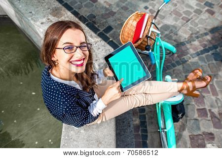 Business Woman Sitting With Tablet On The Fo?ntain In The City With Bicycle On Background