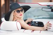 Outdoor summer portrait of stylish blonde vintage woman driving a convertible red retro car. Fashionable attractive fair hair female with black hat in red vehicle. Sunny bright colors, outdoors shot. poster