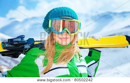 Closeup portrait of cute ski trainer,  active woman wearing a mask and holding in hands ski, active winter vacation, happiness and enjoyment concept