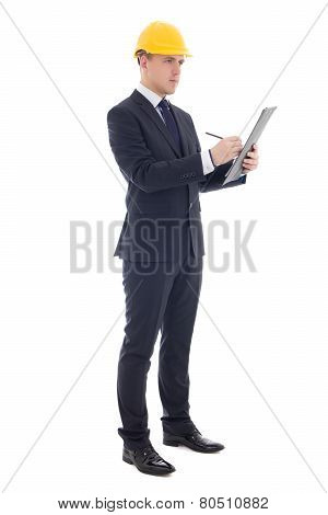 Young Handsome Business Man In Yellow Builder's Helmet Writing Something On Clipboard Isolated On Wh