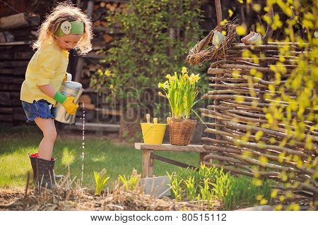 cute child girl playing little gardener and watering flowers in spring garden