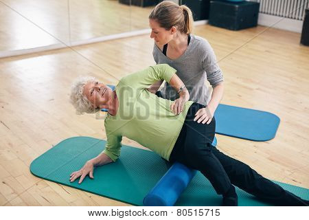 Physical therapists assisting senior woman to perform myofascial release technique with a foam roller. poster