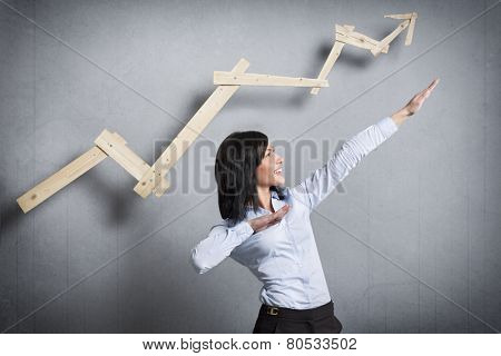 Concept: Successful business trend. Happy talented businesswoman pointing arm upwards in front of ascending business graph, isolated on grey background.