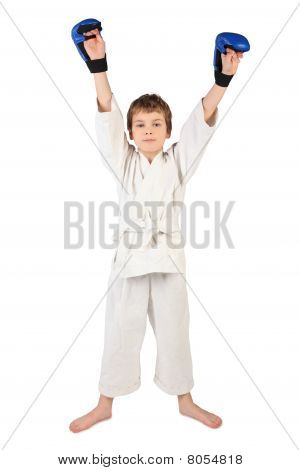 Little Boxer Boy In White Dress And Blue Boxing Gloves Hands Up Looking At Camera