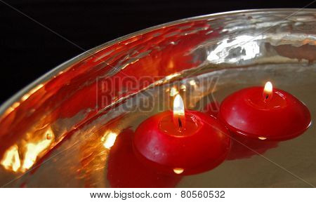 red candles floating in a silver bowl