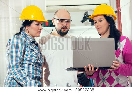 Craftsman and two craftswoman looking at laptop, selective focus