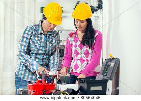 Craftswomen with helmet working together in the workshop