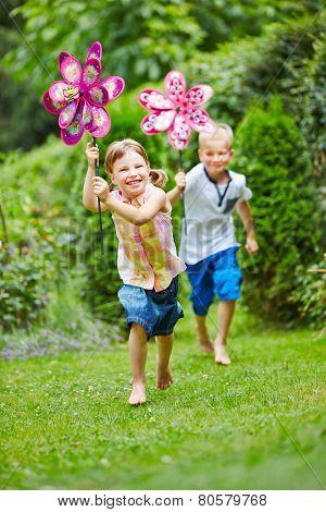 Two happy children running in garden in summer with windmills