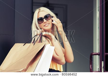 Happy fashion woman with shopping bags calling on mobile phone