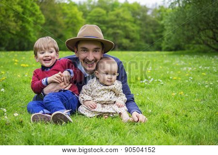 Father And Kids Relaxing In A Park